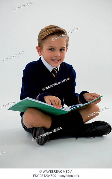 Schoolboy reading book while sitting on white background