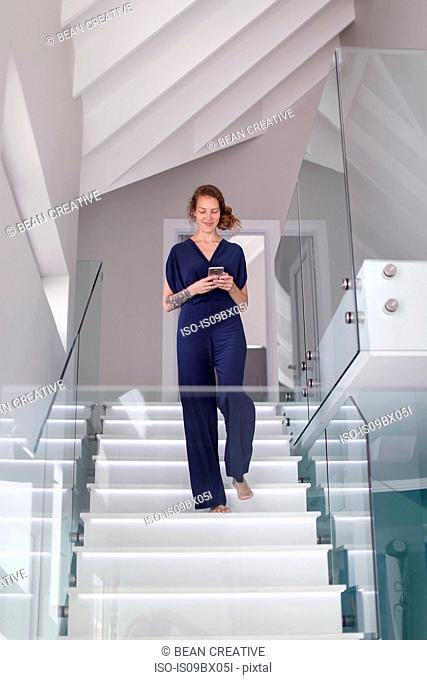 Young woman coming down modern stairway looking at smartphone