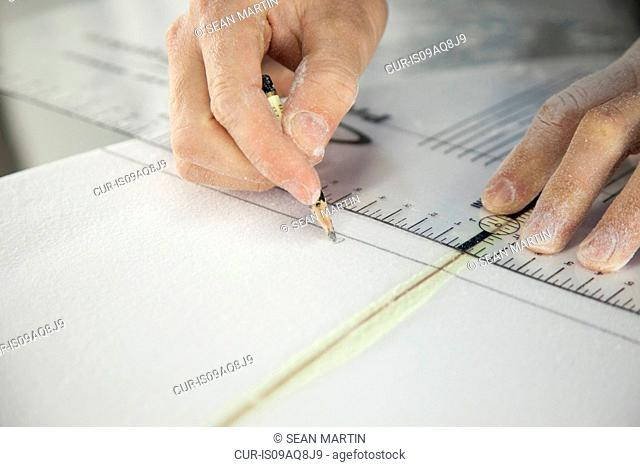 Close up of male surfers hands measuring surfboard in workshop