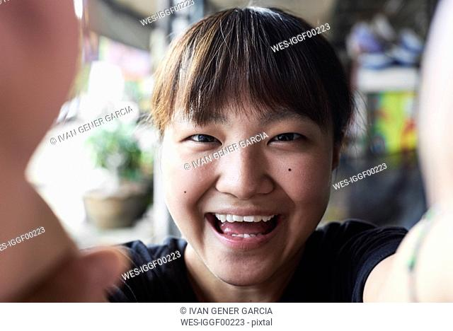 Portrait of laughing woman taking selfie with smartphone