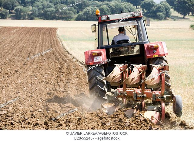 Agricultural machinery. Tractor ploughing the land. Mouldboard plough. Harvesting of cereals, Oco (near Estella), Navarre, Spain