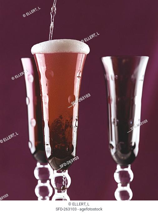 Pouring sparkling wine into red glass