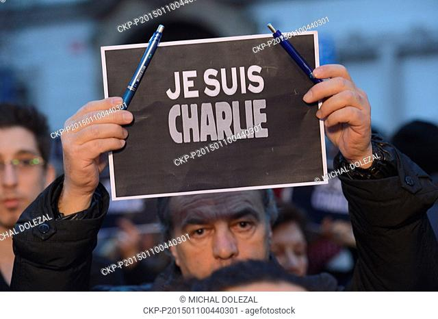 """A man holds a placard reading """"""""Je suis Charlie"""""""" (I Am Charlie) in several languages during a memorial gathering outside French Embassy in Prague"""