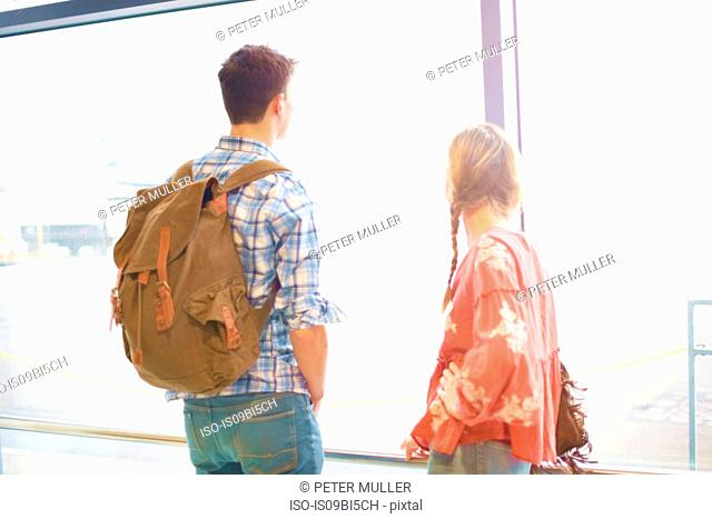 Young couple at airport, carrying backpacks, looking out of window