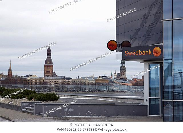 02 March 2019, Latvia, Riga: A branch of the Swedish bank Swedbank can be seen at the foot of a glass office building. In the background you can see the...
