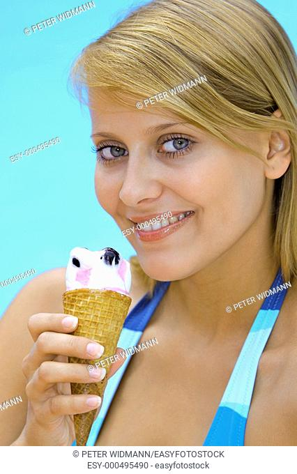 Blonde woman licking an ice cream in the summer holiday by the pool