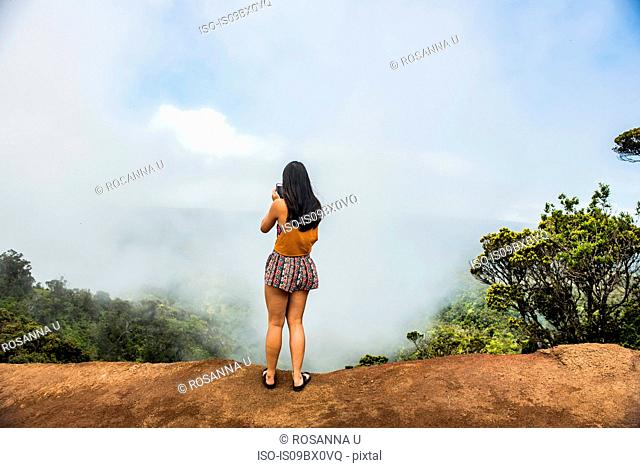 Woman taking photograph of mist, Waimea Canyon, Kauai, Hawaii