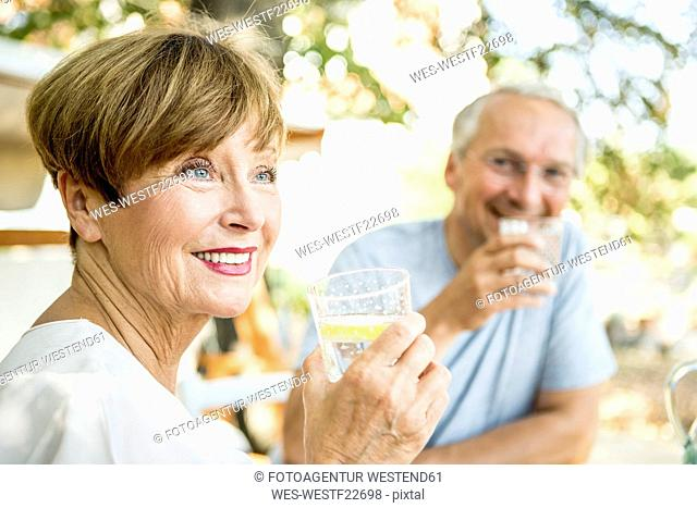 Smiling senior woman drinking glass of water with husband in background