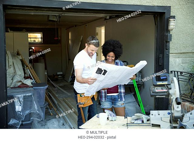 Couple reviewing blueprint for home improvement project outside garage