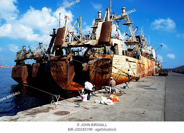 Fishing from the Dique Reina Sofia, Las Palmas harbour, Gran Canaria, Canary islands, Spain, with rusting trawler in background