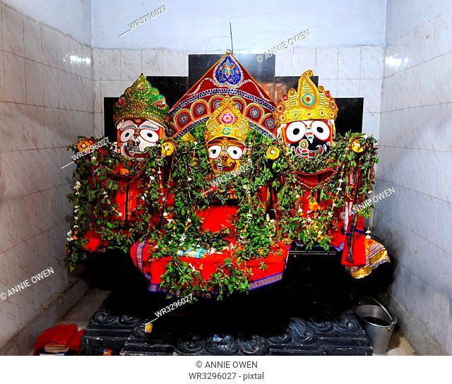 Trio of deities draped with leaf garlands inside temple to Lord Jagannath, rural Odisha, India, Asia