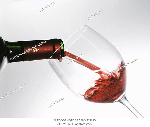 Pouring red wine from a bottle into a glass (1)