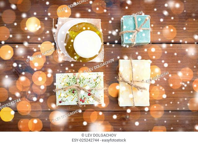 beauty, spa, bodycare, bath and natural cosmetics concept - handmade soap bars on wooden table over lights and snow
