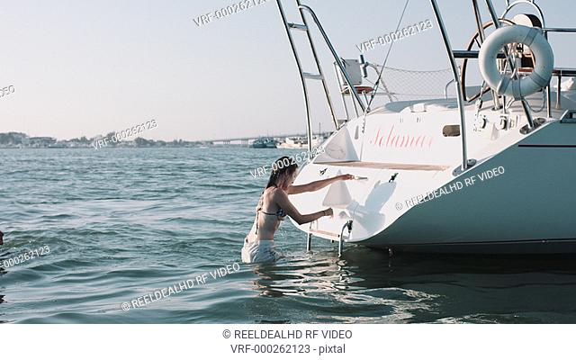 Couple getting out of water then kissing on sailboat