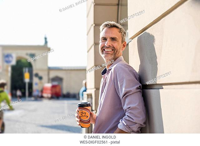 Smiling man with takeaway coffee in the city