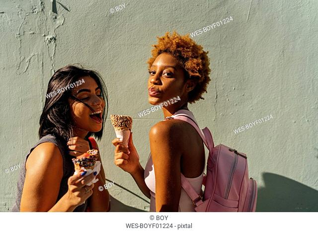 Two happy female friends with ice cream cones posing at a wall