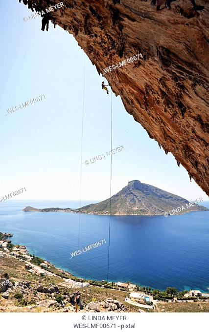 Greece, Kalymnos, climber abseiling in rock wall