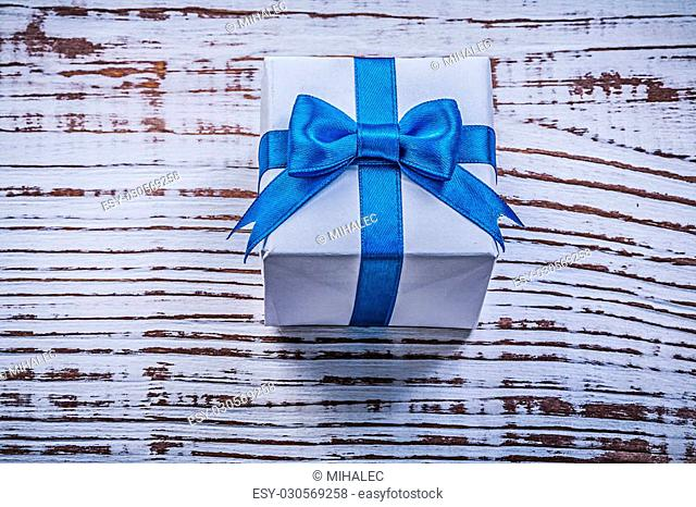 Present box on vintage wooden board top view holidays concept