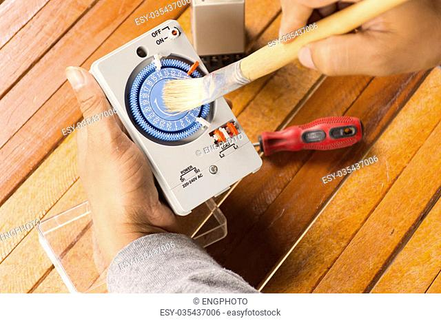 Timer tool with brush in hand of man cleaning on wooden background