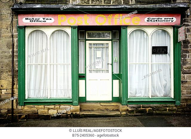 Facade of a closed Post Office with a Open sign in the window, Motor Tax Office, Cards and Stationary, in the Main Street, Addingham, West Yorkshire Dales