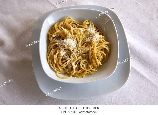 Bowl of Spagetti Carbonara sprinkled with Parmesan Cheese sitting on white tablecloth of outdoor café. Rome, Lazio, Italy