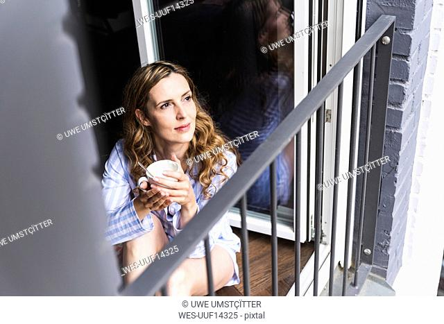 Smiling woman in pyjama at home with cup of coffee looking out of balcony door