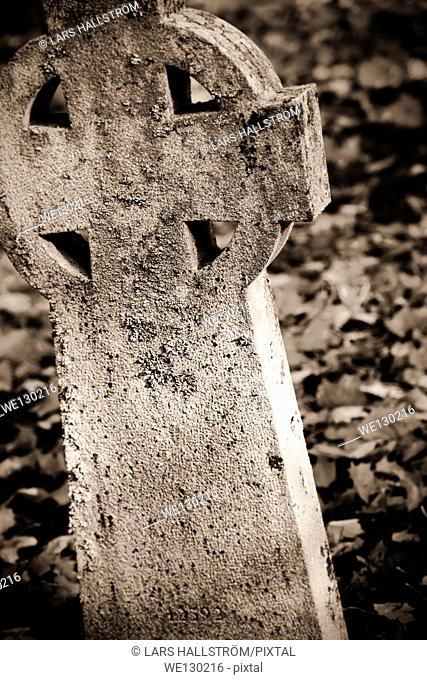 Close up of old tombstone with cross in graveyard, Sweden