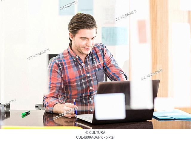 Young businessman looking at laptop on office desk