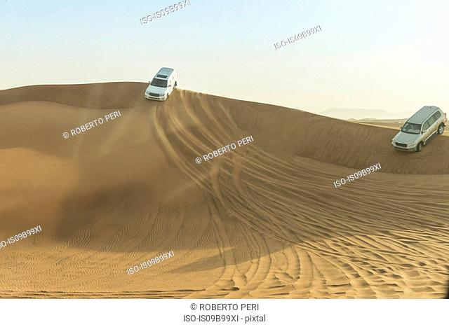 Off road vehicles driving down desert dunes, Dubai, United Arab Emirates