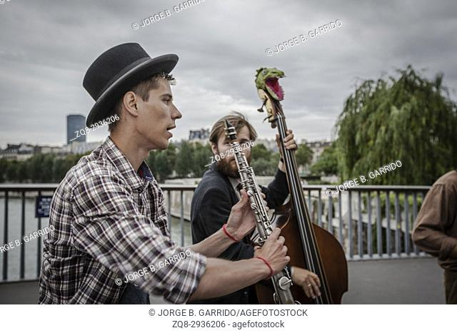 Musicians on the street performing on the bridge connecting the two small islands, Cite and Saint Louis. Paris, France