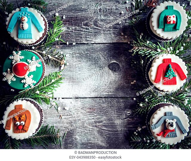 Homemade Christmas cupcakes on wooden background with blank space in the middle