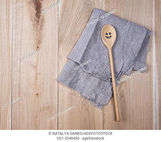 folded gray towel and spoon on brown wooden background, top view