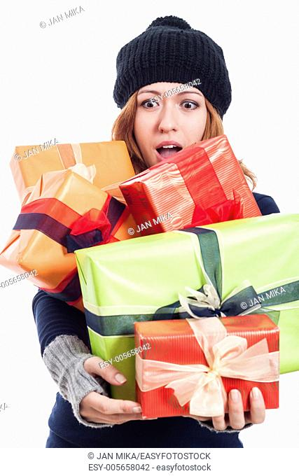 Surprised woman in winter hat holding many presents, isolated on white background