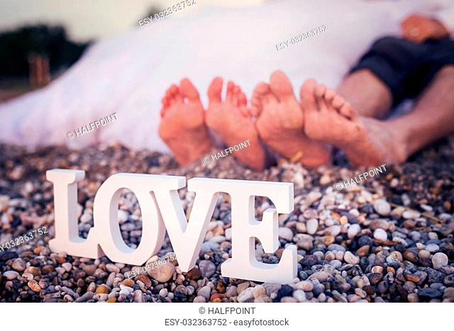 Feet of a bride and groom sitting on a beach