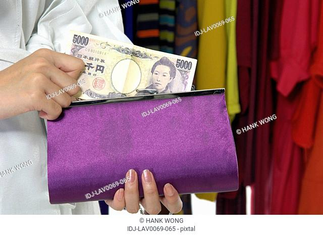 Woman holding paper currency and purse in a clothing store