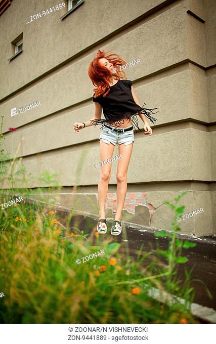 Young beautiful woman jumping waving hair