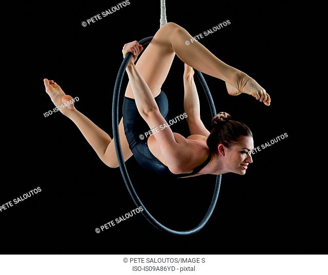 Aerialist performing on hoop in front of black background