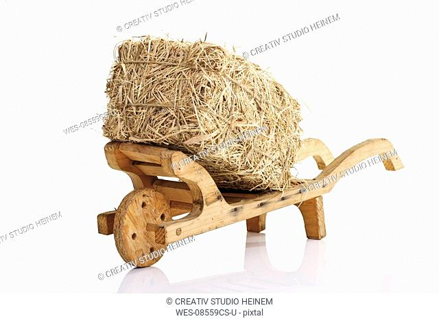 Wooden wheelbarrow and bale of straw