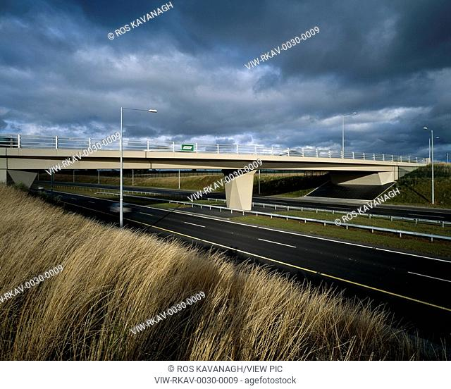 M4 Airport Interchange Bridges, Dublin, Ireland. Architect: Grafton Architects, 2003. View of bridge from side of motorway showing concrete supports