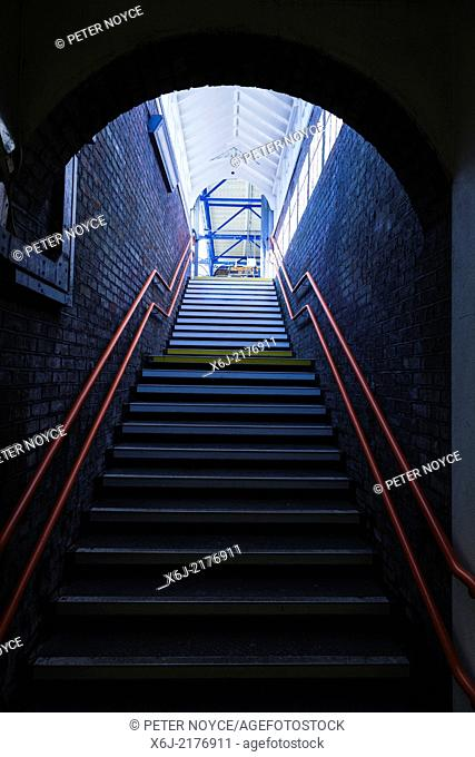Steps up leading from dark to light with red hand rail