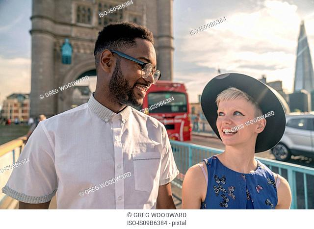 Young couple walking outdoors, Tower Bridge in background