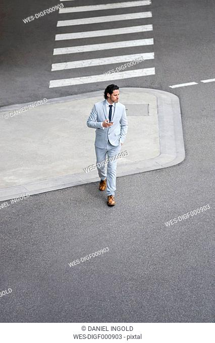 Walking businessman with smartphone crossing street