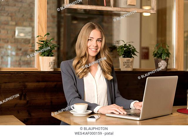 Portrait of smiling young woman using laptop in a coffee shop