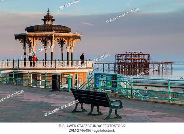 Late summer sunset on Brighton seafront, East Sussex, England. The Bandstand and West Pier ruins in the background