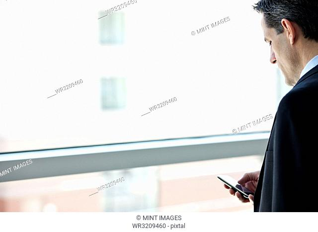 Caucasian businessman checking his cell phone in a conference centre lobby