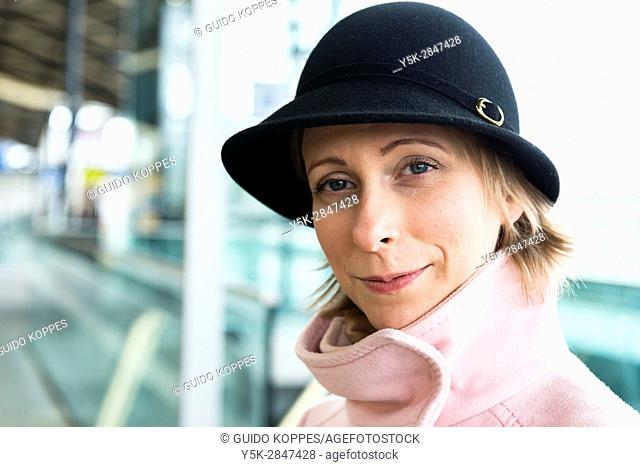 Tilburg, Netherlands. Young adult caucasian female waiting for her intercity train to take her to her work assignment as a musci teacher