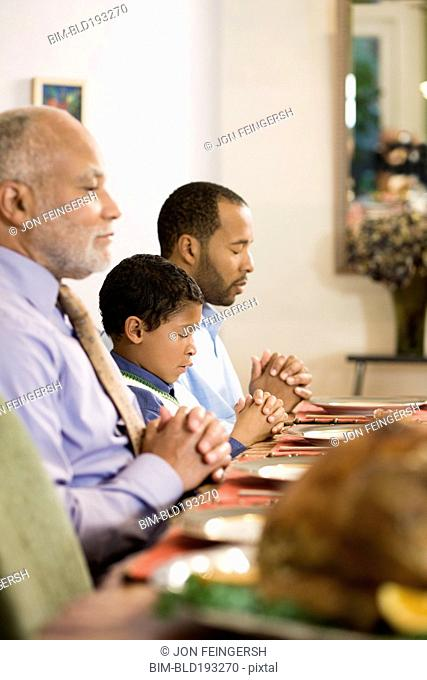 African American family saying grace at dinner table