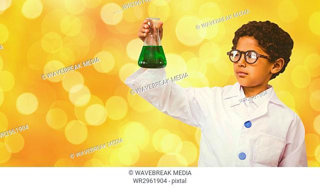 Little boy analyzing solution in beaker