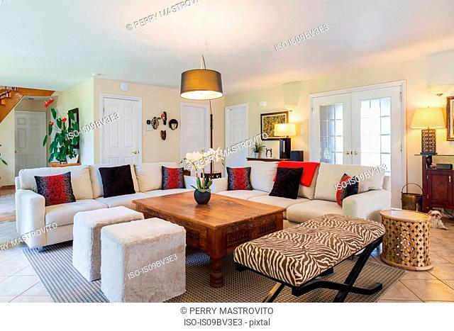 Beige upholstered sofas with colourful cushions, wooden coffee table and zebra motif ottoman in living room