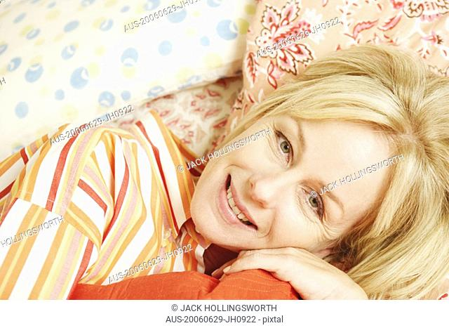 Portrait of a mature woman lying in bed and smiling
